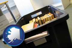 ak map icon and a moving box in an empty office, during a relocation project
